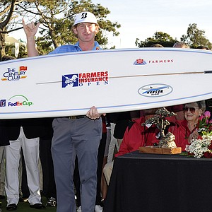 Brandt Snedeker poses with Farmers Insurance CEO Jeff Dailey, right, and the winner's trophy and surfboard after his playoff victory at the Farmers Insurance Open.