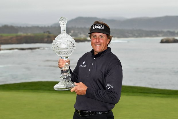 Phil Mickelson celebrates with the tournament trophy after winning with an eight-under-par 64 during the AT&T Pebble Beach National Pro-Am at Pebble Beach.