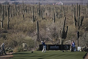 Dustin Johnson tees off on four as Jim Furyk, left, waits in the first round during the Match Play Championship.