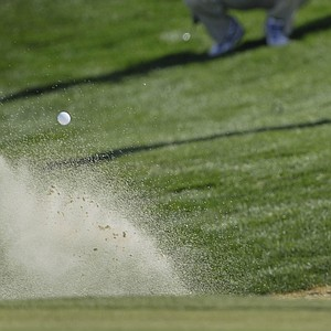 Tiger Woods hits out of the sand trap on the third green during the first round of the Match Play Championship golf tournament.