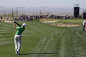 Tiger Woods hits an approach shot from the second fairway after hitting a left-handed shot out of the rough during the Match Play Championship.
