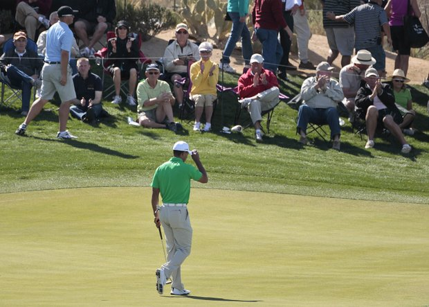 Tiger Woods tips his hat to the crowd after sinking a putt to win the third hole against Gonzalo Fernandez-Castano during the Match Play Championship.