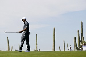 Tiger Woods lines up his shot on the fourth green while playing Nick Watney during the Match Play Championship.