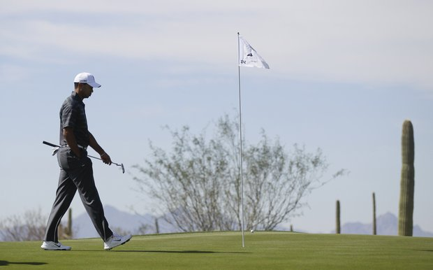 Tiger Woods walks along the fourth green before putting against Nick Watney during the Match Play Championship.