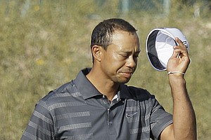 Tiger Woods removes his cap after missing a putt on No. 18 to lose the match to Nick Watney during the second round of the Match Play Championship.