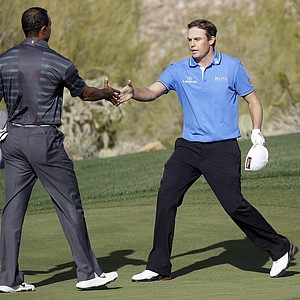 Nick Watney, right, shakes hands with Tiger Woods after beating him 1-up during the Match Play Championship.