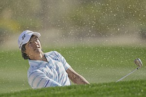 Japan's Ryo Ishikawa hits out of a bunker on the second fairway while playing Scotland's Paul Lawrie during the Match Play Championship.