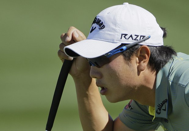 South Korea's Sang-moon Bae lines up a putt on three while playing Charl Schwartzel during the Match Play Championship
