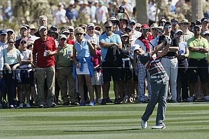 Northern Ireland's Rory McIlroy hits off the first fairway with the gallery following along behind as he plays Hunter Mahan in the final round of the Match Play Championship.