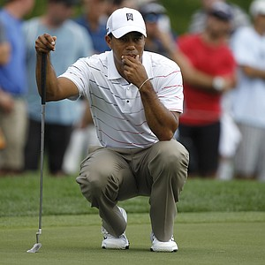 Tiger Woods lines up a putt on the second green during the first round of the Honda Classic.