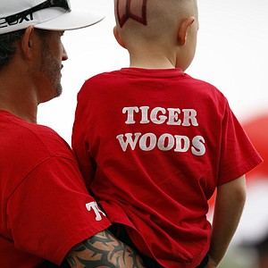 Chris Siska and his 4-year-old son Chris, watch Tiger Woods play during the first round of the Cadillac Championship.