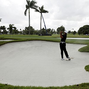 Tiger Woods hits out of a bunker at the eighth hole.