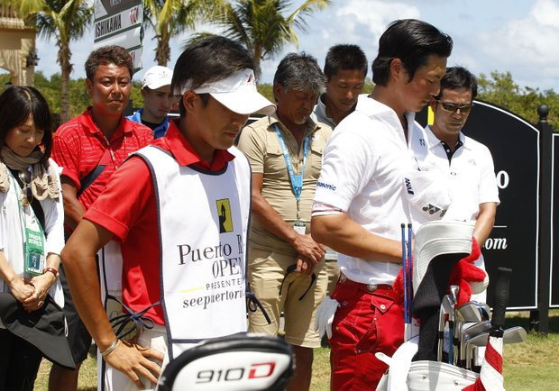 Ryo Ishikawa, right, stands with his caddie Hiroyuki Kato and members of the media to observe a moment of silence on the first anniversary of the earthquake that devastated Japan during the final round of the Puerto Rico Open.