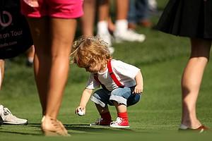 Team Isleworth Daniel Chopra's little boy, Casper, plays near the 18th green on Tuesday during the Tavistock Cup.