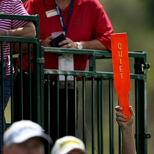 A volunteer holds the quiet paddle at No. 18 during the first round of the Arnold Palmer Invitational.