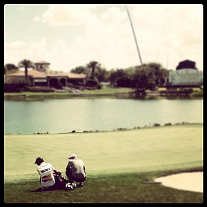 Nick Watney and his caddie wait at No. 18 during the first round. Watney posted a 68.
