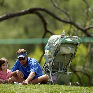 Jason Lusk and his daughter Amelia Marie Lusk, 4, of Ocoee, find a quiet spot to take a break from the heat and action during the third round of the Arnold Palmer Invitational.