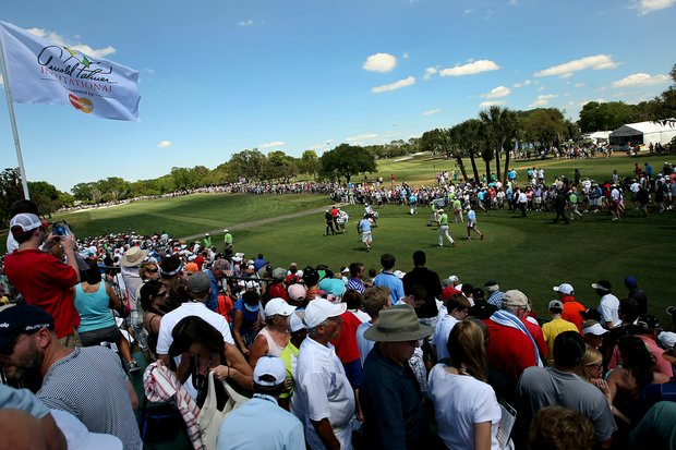 Crowds make their way as Tiger Woods and Graeme McDowell make their way down the first tee during the the final round of the Arnold Palmer Invitational.