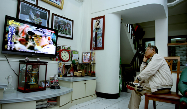 "Yani Tseng's dad, Mao-Shin ""Charlie"" watches a biography of Yani in his living room."