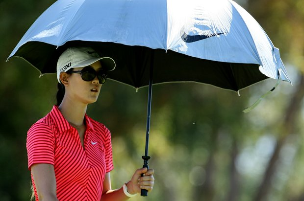Michelle Wie uses an umbrella to shield herself from the sun on Friday at the Kraft Nabisco Championship.