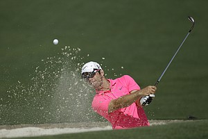 Paul Casey, of England, hits out of a trap on the second hole during a practice round for the Masters.