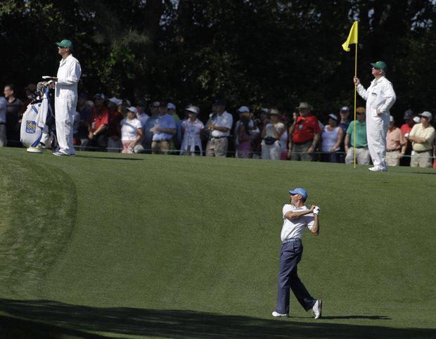 Caddies watch Matt Kuchar's hit on the fifth fairway during a practice round for the Masters.