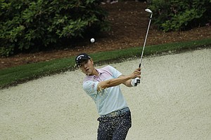 Sang-Moon Bae, of Korea, chips to the 13th green during a practice round for the Masters.