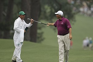 Fred Couples hands his club to his caddie on the eighth fairway during a practice round for the Masters.