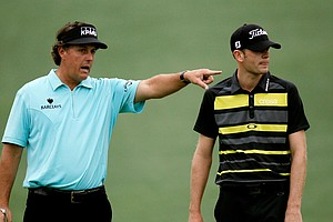 Phil Mickelson (L) and Brendan Steele look at a shot on the green during a practice round prior to the start of the 2012 Masters Tournament at Augusta National.