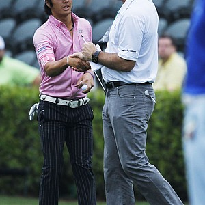 Ryo Ishikawa, of Japan, shakes hands with former three-time Masters champion Nick Faldo, right, before a practice round for the Masters.