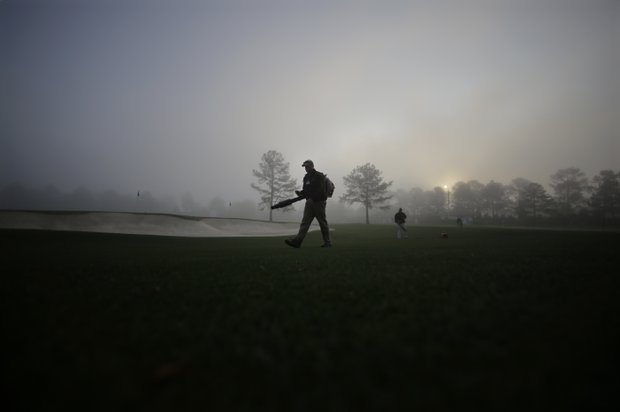 Course worker Kyle Johnson blows debris from an overnight storm on the mist covered driving range before practice rounds for the Masters.