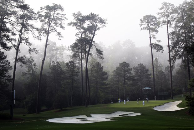 Players putt on the 10th green in the morning fog during a practice round for the Masters on Wednesday.