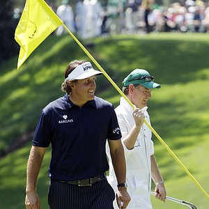 Phil Mickelson and his caddie Jim Mackay talk to spectators on the first green during the par three competition at the Masters.