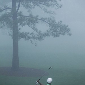 Tiger Woods hits from a fog shrouded driving range before his practice round for the Masters.