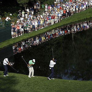 From left, Mark O'Meara, Tiger Woods and Sean O'Hair skip golf balls across the pond on the 16th hole during a practice round for the Masters.