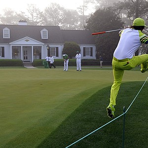 Rickie Fowler hurdles a rope to get to the next tee at Augusta National.