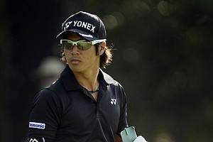 Ryo Ishikawa, of Japan, checks his course notes on the first fairway during a practice round for the Masters.