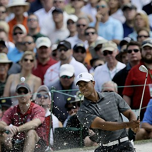 Tiger Woods chips out of a bunker on the seventh hole during the first round the Masters.
