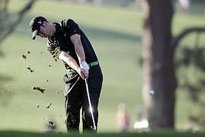 Ross Fisher, of England, hits on the first fairway during the first round of the Masters.