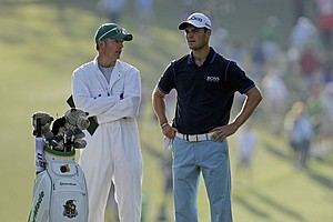 Martin Kaymer, of Germany, talks to his caddie Christain Donald before hitting on the first fairway during the first round of the Masters.