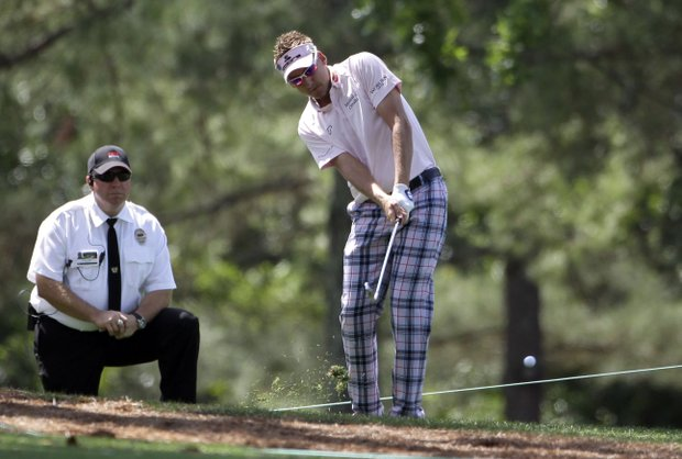 Ian Poulter, of England, hits his second shot out of the rough on the first hole during the first round of the Masters.