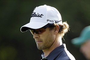 Adam Scott, of Australia, examines his putter as he walks down the first fairway during the first round of the Masters.