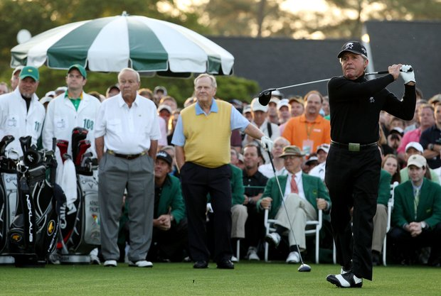 Honorary starter Gary Player of South Africa hits a tee shot as Arnold Palmer (L) and Jack Nicklaus (C) stand on the tee box at the start of the first round of the 2012 Masters Tournament at Augusta National.
