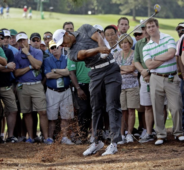 Tiger Woods hits out of the rough off the first fairway during the first round the Masters.