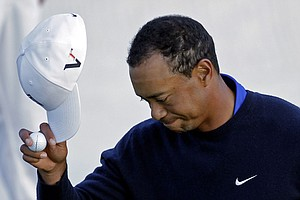 Tiger Woods tips his cap on the 18th green after finishing his second round of the Masters.
