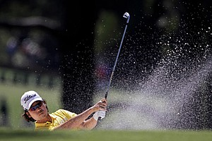 Kevin Na hits out of a bunker on the on the second hole during the third round of the Masters.
