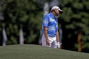 Sergio Garcia, of Spain, reacts after hitting into a sand trap on the first fairway during the third round of the Masters.