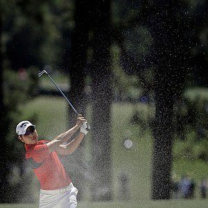 Sang-Moon Bae, of South Korea, hits off the first fairway during the fourth round of the Masters.