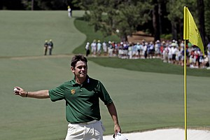Louis Oosthuizen, of South Africa, throws his ball to a spectator after hitting a double-eagle two on the par 5 second hole during the fourth round of the Masters.