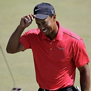 Tiger Woods tips his cap after putting out on the 18th green during the fourth round of the Masters.